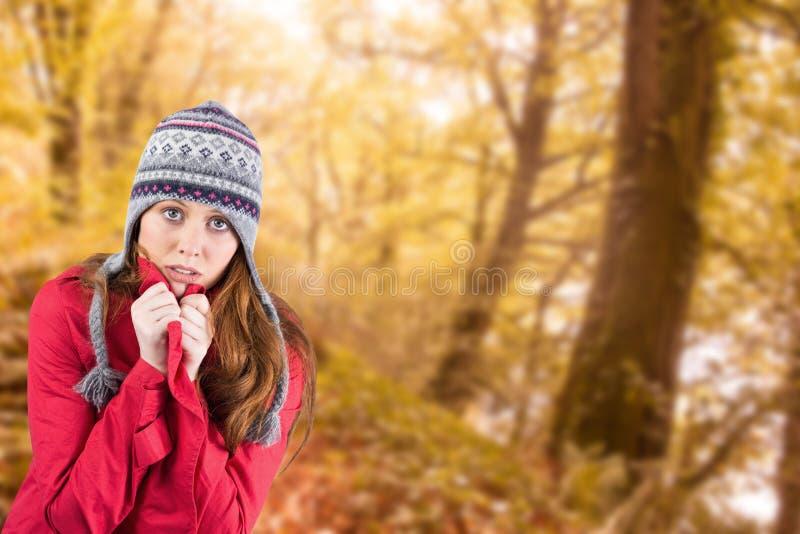 Σύνθετη εικόνα του κρύων redhead φορώντας παλτού και του καπέλου στοκ εικόνες