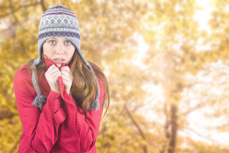 Σύνθετη εικόνα του κρύων redhead φορώντας παλτού και του καπέλου στοκ φωτογραφία