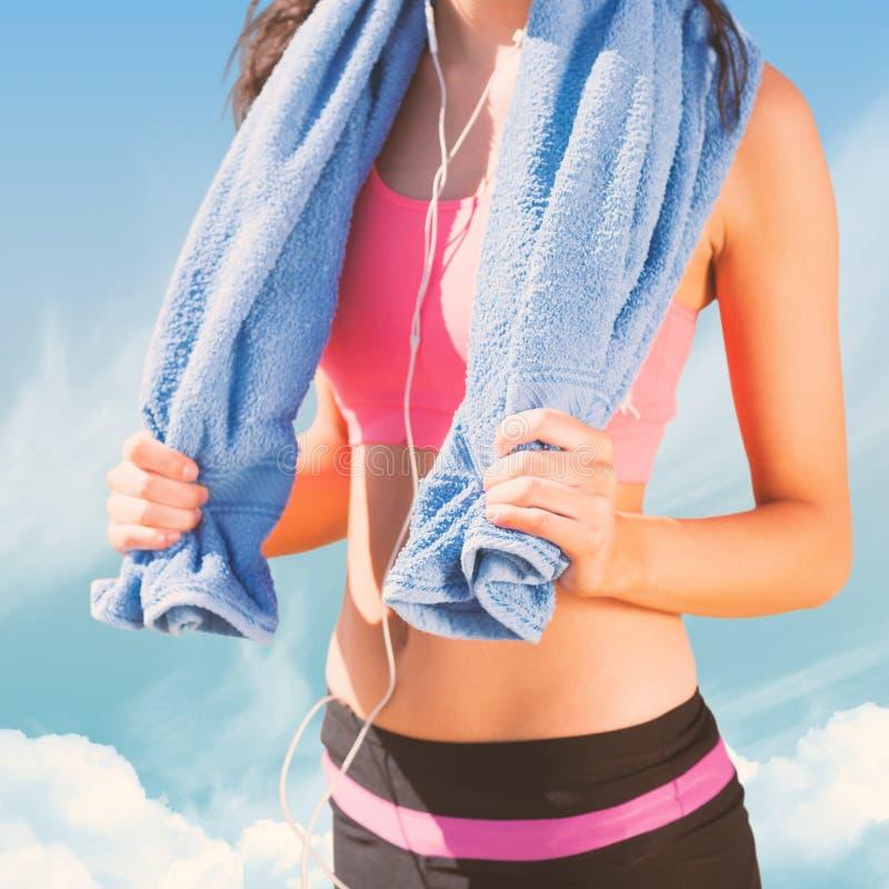 Σύνθετη εικόνα του μέσου τμήματος της υγιούς γυναίκας με την πετσέτα γύρω από το λαιμό στην παραλία στοκ φωτογραφίες