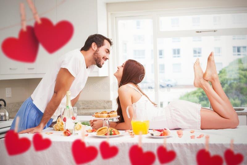 Σύνθετη εικόνα του νέου ζεύγους που έχει ένα ρομαντικό πρόγευμα στοκ εικόνα με δικαίωμα ελεύθερης χρήσης