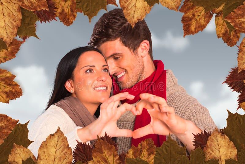 Σύνθετη εικόνα του νέου ζεύγους που κατασκευάζει την καρδιά με τα χέρια στοκ φωτογραφίες