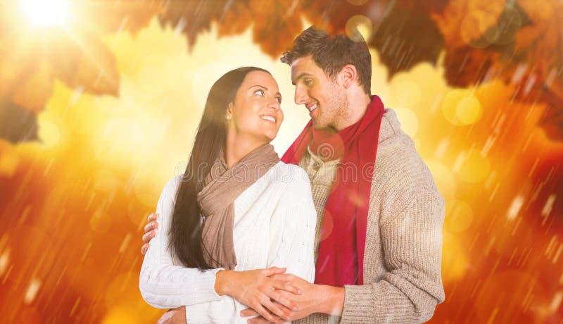 Σύνθετη εικόνα του νέου ζεύγους που χαμογελά και που αγκαλιάζει στοκ φωτογραφία με δικαίωμα ελεύθερης χρήσης