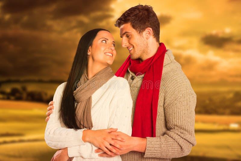 Σύνθετη εικόνα του νέου ζεύγους που χαμογελά και που αγκαλιάζει στοκ φωτογραφία