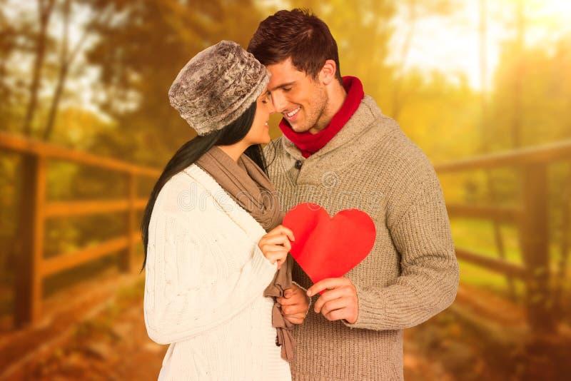Σύνθετη εικόνα του νέου ζεύγους που χαμογελά και που αγκαλιάζει στοκ εικόνες
