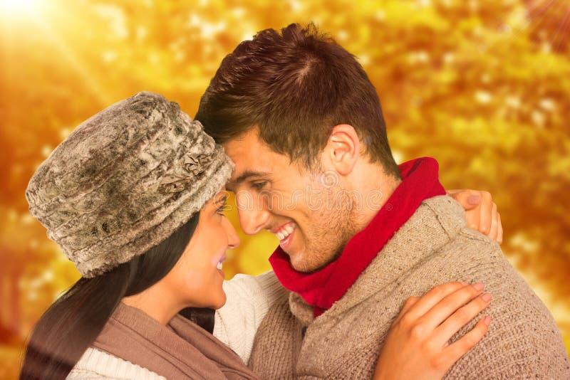 Σύνθετη εικόνα του νέου ζεύγους που χαμογελά και που αγκαλιάζει στοκ φωτογραφίες με δικαίωμα ελεύθερης χρήσης
