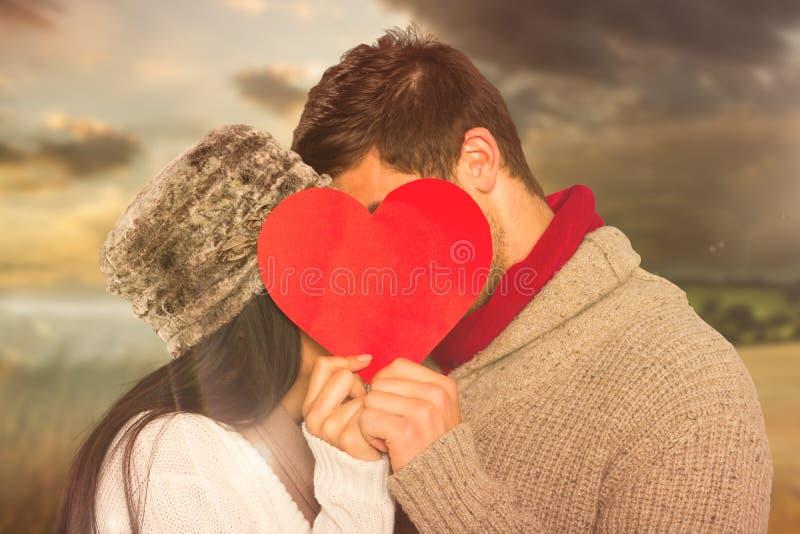 Σύνθετη εικόνα του νέου φιλήματος ζευγών πίσω από την κόκκινη καρδιά στοκ εικόνες