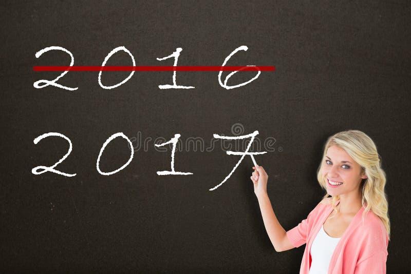 Σύνθετη εικόνα του νέου όμορφου γραψίματος σπουδαστών με την κιμωλία στοκ εικόνα