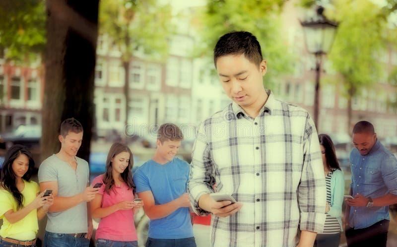 Σύνθετη εικόνα του νεαρού άνδρα που χρησιμοποιεί το έξυπνο τηλέφωνο στοκ φωτογραφία