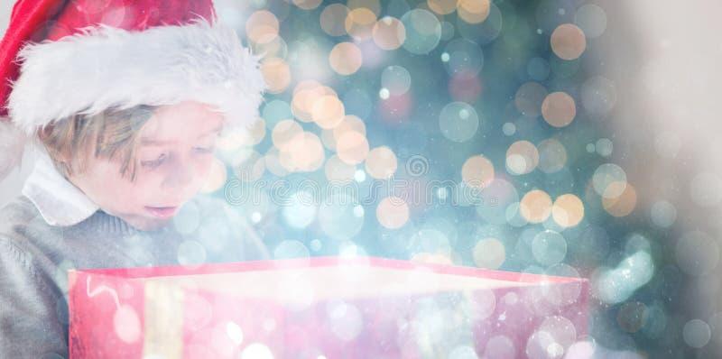Σύνθετη εικόνα του παιδιού που ανοίγει το χριστουγεννιάτικο δώρο του στοκ εικόνα με δικαίωμα ελεύθερης χρήσης