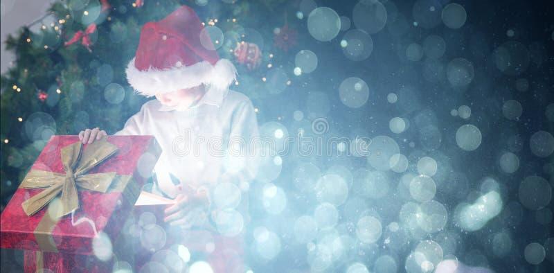 Σύνθετη εικόνα του παιδιού που ανοίγει το χριστουγεννιάτικο δώρο του στοκ φωτογραφίες με δικαίωμα ελεύθερης χρήσης
