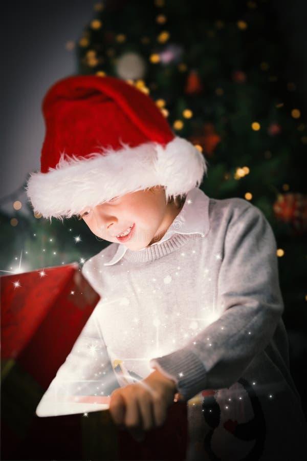 Σύνθετη εικόνα του παιδιού που ανοίγει το χριστουγεννιάτικο δώρο του στοκ εικόνες