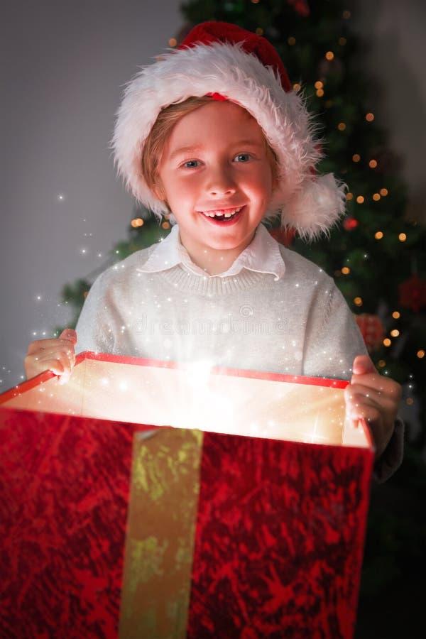 Σύνθετη εικόνα του παιδιού που ανοίγει το χριστουγεννιάτικο δώρο του στοκ φωτογραφίες
