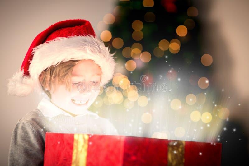 Σύνθετη εικόνα του παιδιού που ανοίγει το χριστουγεννιάτικο δώρο του στοκ εικόνα