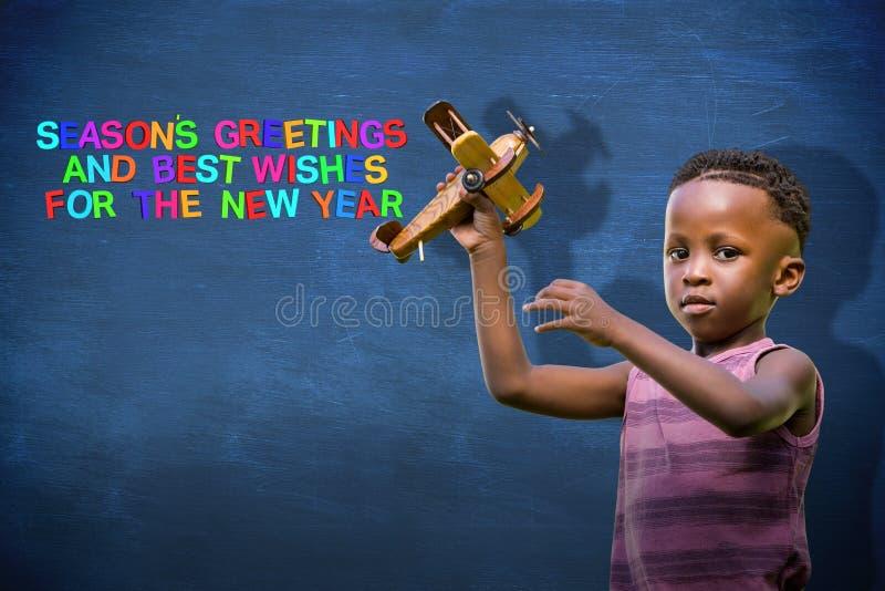 Σύνθετη εικόνα του παιδιού που κρατά το ξύλινο αεροπλάνο στοκ εικόνα
