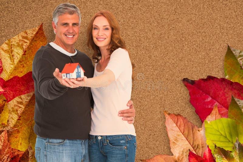 Σύνθετη εικόνα του περιστασιακού ζεύγους που κρατά το μικρό σπίτι στοκ εικόνα με δικαίωμα ελεύθερης χρήσης