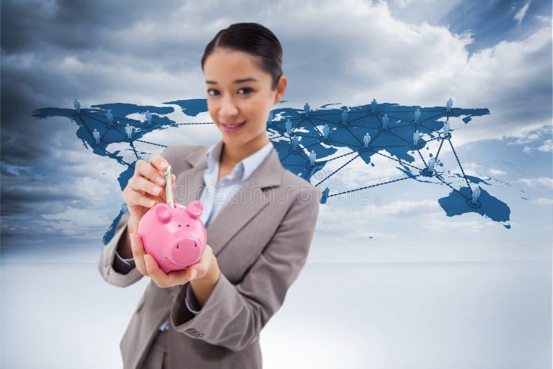 Σύνθετη εικόνα του πορτρέτου μιας επιχειρηματία που βάζει ένα τραπεζογραμμάτιο σε μια piggy τράπεζα στοκ φωτογραφία