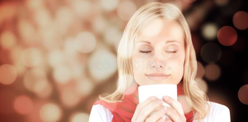 Σύνθετη εικόνα του πορτρέτου μιας νέας γυναίκας που απολαμβάνει τον καυτό καφέ της το χειμώνα στοκ εικόνα