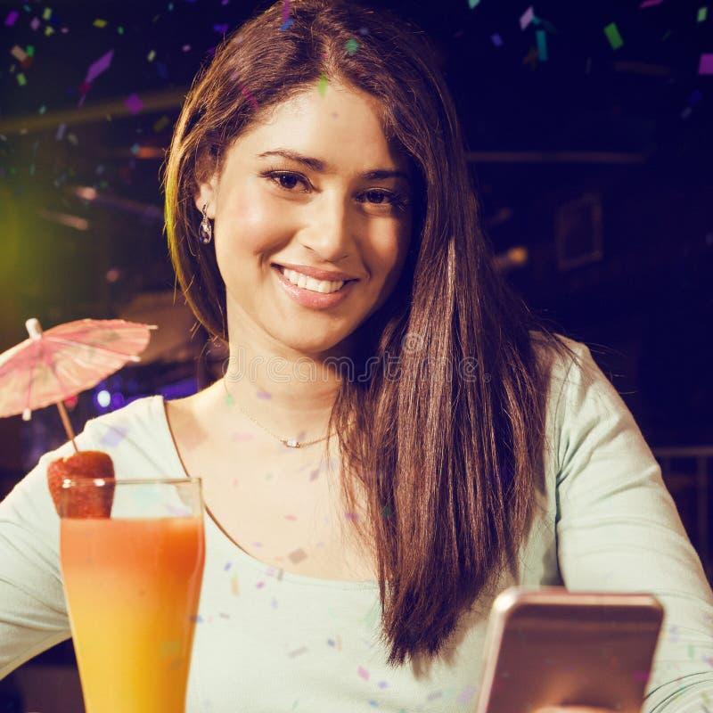 Σύνθετη εικόνα του πορτρέτου του μηνύματος κειμένου δακτυλογράφησης γυναικών ενώ έχοντας το κοκτέιλ στοκ φωτογραφίες με δικαίωμα ελεύθερης χρήσης