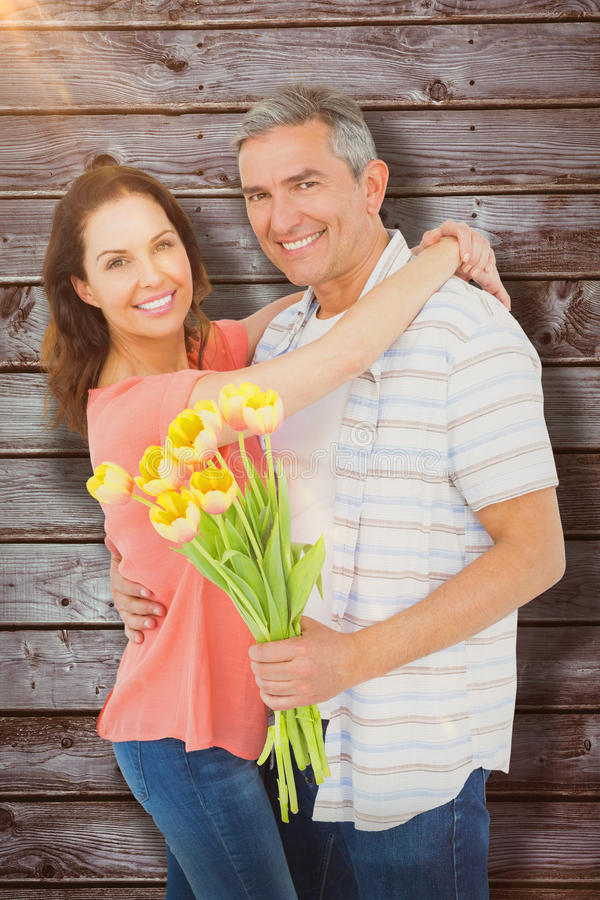 Σύνθετη εικόνα του πορτρέτου του χαμογελώντας ζεύγους με την ανθοδέσμη λουλουδιών στοκ φωτογραφία