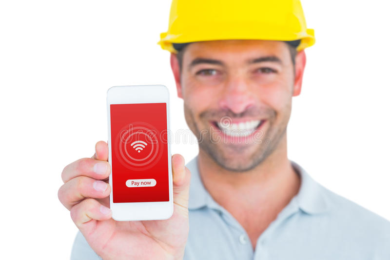 Σύνθετη εικόνα του πορτρέτου του χαμόγελου του handyman παρουσιάζοντας έξυπνου τηλεφώνου ελεύθερη απεικόνιση δικαιώματος