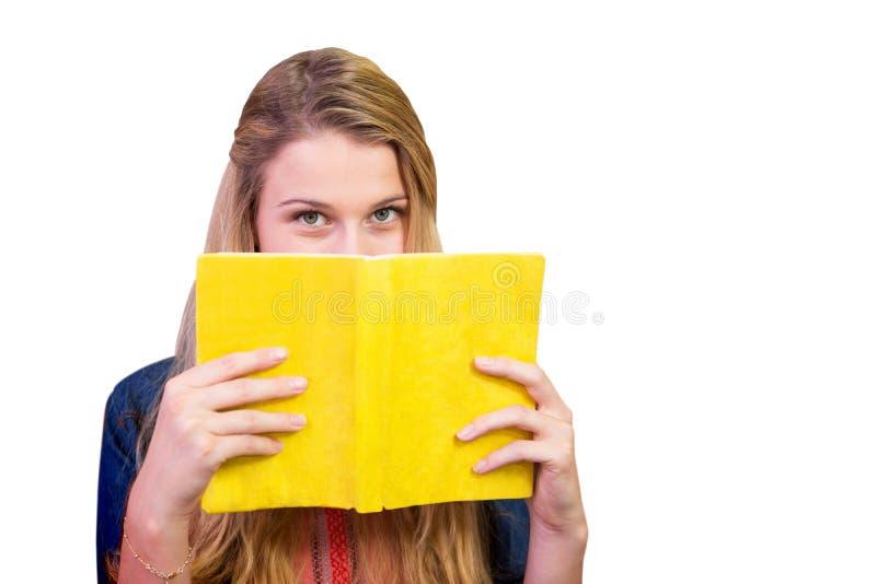 Σύνθετη εικόνα του σπουδαστή που καλύπτει το πρόσωπο με το βιβλίο στη βιβλιοθήκη στοκ φωτογραφία