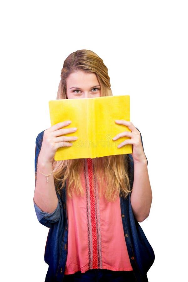 Σύνθετη εικόνα του σπουδαστή που καλύπτει το πρόσωπο με το βιβλίο στη βιβλιοθήκη στοκ φωτογραφίες