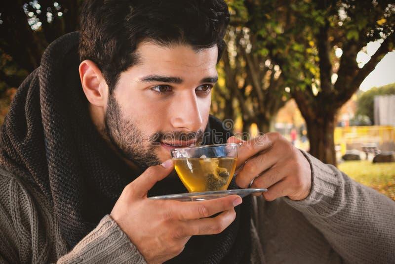 Σύνθετη εικόνα του στοχαστικού ατόμου που έχει το τσάι λεμονιών στοκ εικόνα