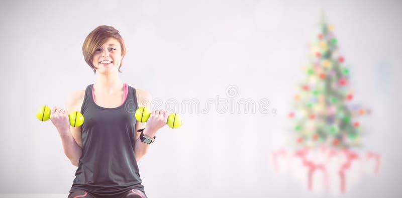 Σύνθετη εικόνα του φίλαθλου χαμόγελου γυναικών ανυψωτικών τους αλτήρες στοκ φωτογραφία με δικαίωμα ελεύθερης χρήσης