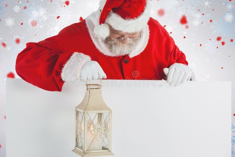 Σύνθετη εικόνα του φαναριού Χριστουγέννων εκμετάλλευσης Άγιου Βασίλη στο λευκό πίνακα στοκ φωτογραφίες