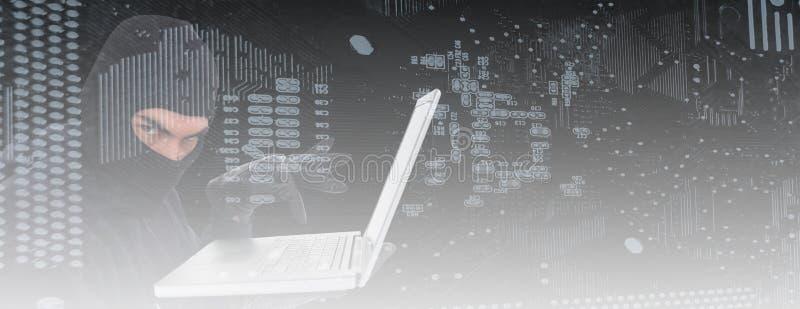 Σύνθετη εικόνα του χάκερ balaclava που στέκεται και που δακτυλογραφεί στο lap-top ελεύθερη απεικόνιση δικαιώματος