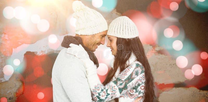 Σύνθετη εικόνα του χαμογελώντας ζεύγους που αγκαλιάζει και που εξετάζει το ένα το άλλο στοκ φωτογραφία