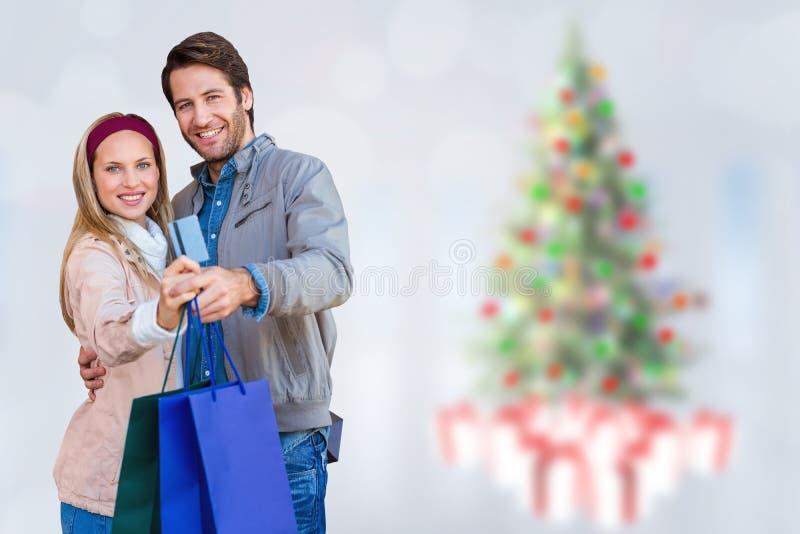 Σύνθετη εικόνα του χαμογελώντας ζεύγους που παρουσιάζει τσάντες πιστωτικών καρτών και αγορών στοκ φωτογραφία με δικαίωμα ελεύθερης χρήσης