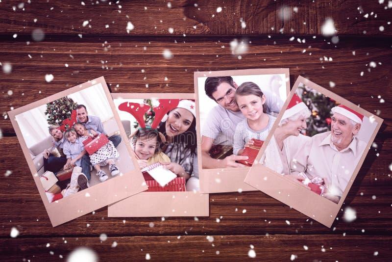 Σύνθετη εικόνα του χαμογελώντας μικρού κοριτσιού με τον πατέρα της που κρατά ένα δώρο Χριστουγέννων στοκ εικόνα