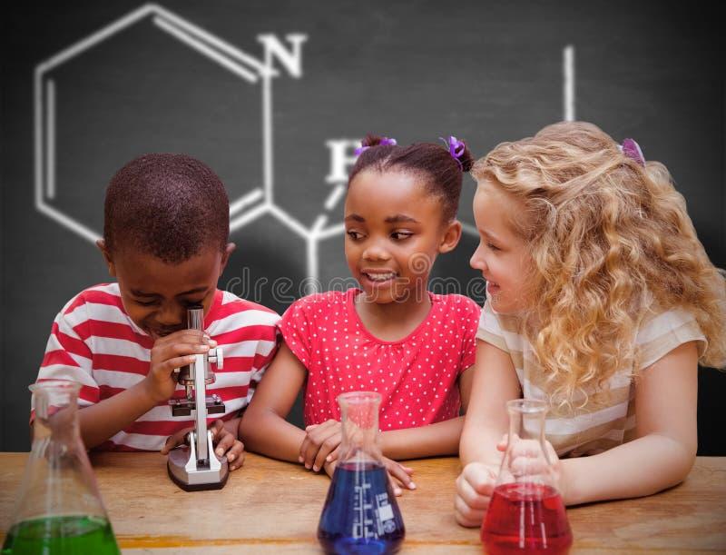 Σύνθετη εικόνα του χαριτωμένου κοιτάγματος μαθητών μέσω του μικροσκοπίου στοκ εικόνα με δικαίωμα ελεύθερης χρήσης