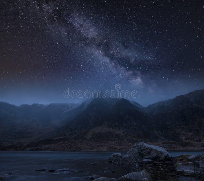 Σύνθετη εικόνα του χειμερινού τοπίου της χιονοσκεπούς σειράς βουνών τη νύχτα με το γαλακτώδη τρόπο ανωτέρω στοκ εικόνες
