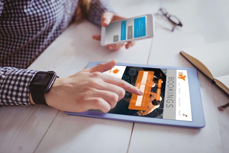 Σύνθετη εικόνα του χεριού που χρησιμοποιεί την ταμπλέτα και το smartphone στοκ εικόνα