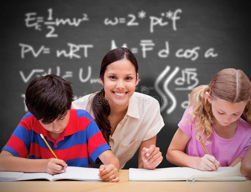 Σύνθετη εικόνα του όμορφου δασκάλου που βοηθά τους μαθητές στη βιβλιοθήκη στοκ φωτογραφίες