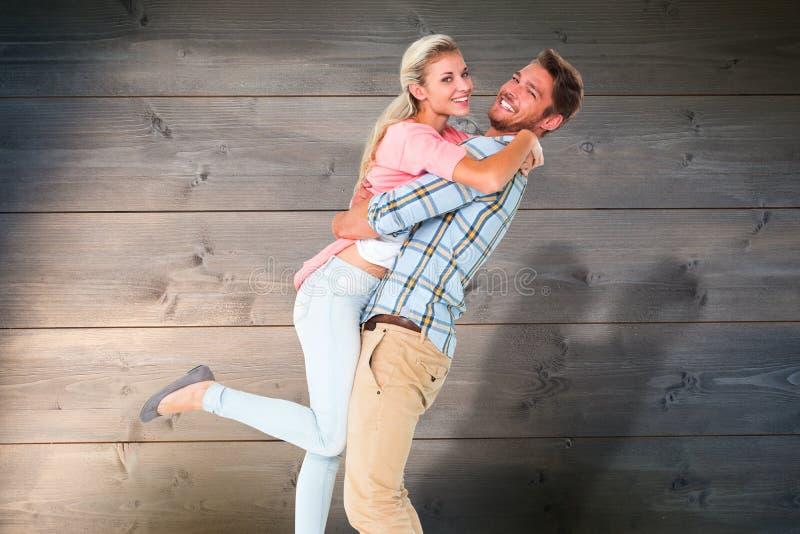 Σύνθετη εικόνα του όμορφου ατόμου που παίρνει και που αγκαλιάζει τη φίλη του στοκ εικόνα