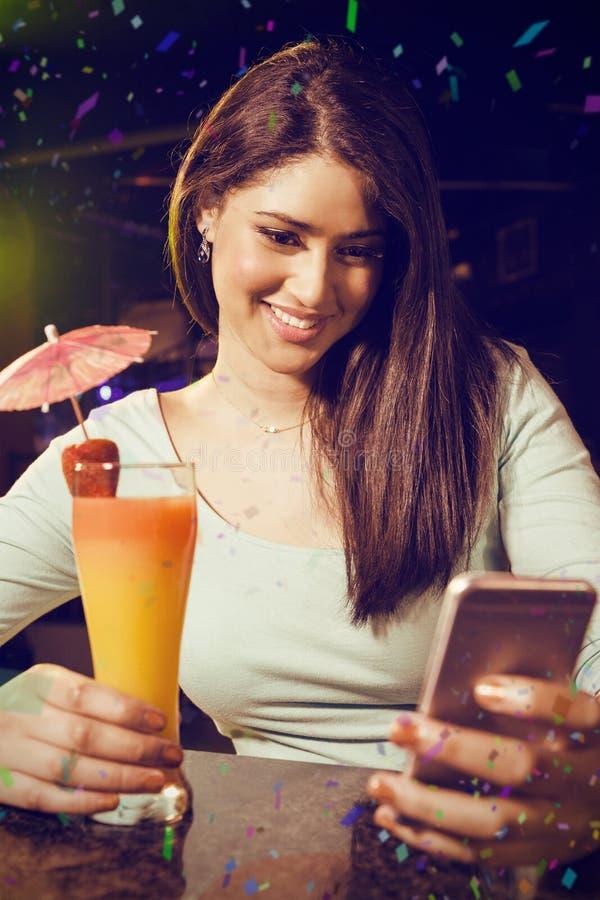 Σύνθετη εικόνα του όμορφου μηνύματος κειμένου δακτυλογράφησης γυναικών ενώ έχοντας το κοκτέιλ στοκ φωτογραφίες με δικαίωμα ελεύθερης χρήσης