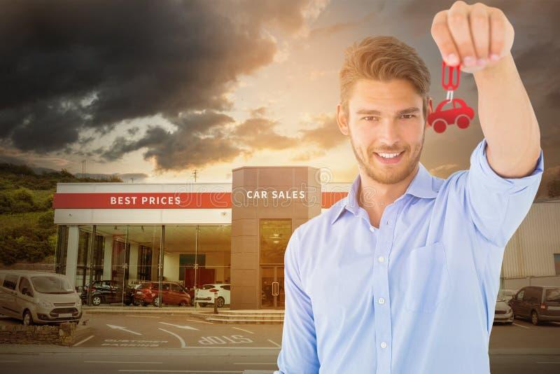 Σύνθετη εικόνα του όμορφου νεαρού άνδρα που παρουσιάζει κλειδί καινούργιων σπιτιών στοκ φωτογραφία με δικαίωμα ελεύθερης χρήσης