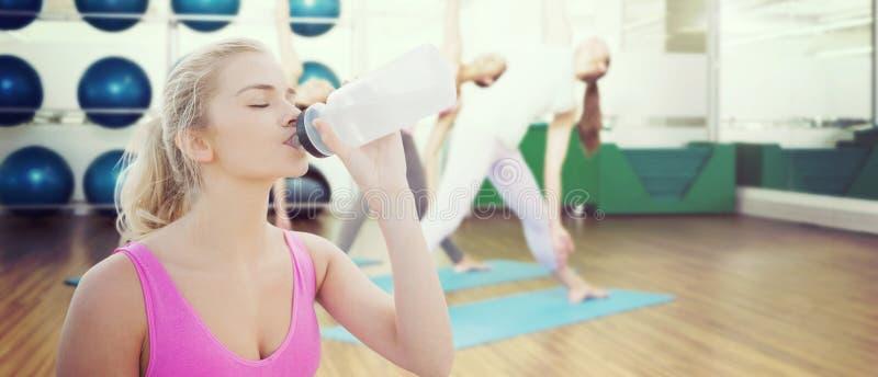 Σύνθετη εικόνα του όμορφου υγιούς πόσιμου νερού γυναικών στοκ εικόνα