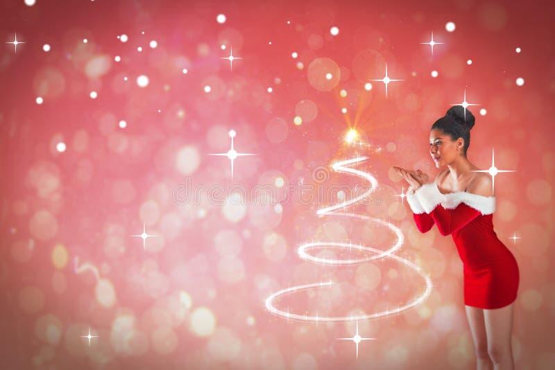 Σύνθετη εικόνα του όμορφου φυσήγματος κοριτσιών santa πέρα από τα χέρια της στοκ εικόνα