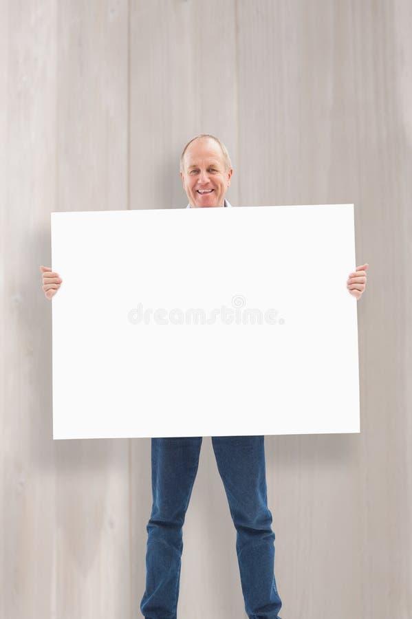 Σύνθετη εικόνα του ώριμου ατόμου που χαμογελά στη κάμερα και που κρατά την κάρτα στοκ φωτογραφία με δικαίωμα ελεύθερης χρήσης