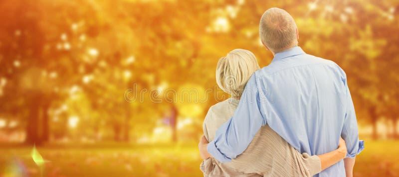 Σύνθετη εικόνα του ώριμου ζεύγους που αγκαλιάζει και που κοιτάζει στοκ εικόνες