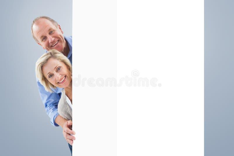 Σύνθετη εικόνα του ώριμου ζεύγους που χαμογελά πίσω από τον τοίχο στοκ εικόνες