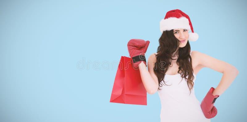 Σύνθετη εικόνα του brunette ομορφιάς στα εγκιβωτίζοντας γάντια με την τσάντα αγορών στοκ εικόνα