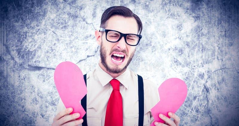 Σύνθετη εικόνα του geeky hipster που φωνάζει και που κρατά τη σπασμένη κάρτα καρδιών στοκ φωτογραφίες