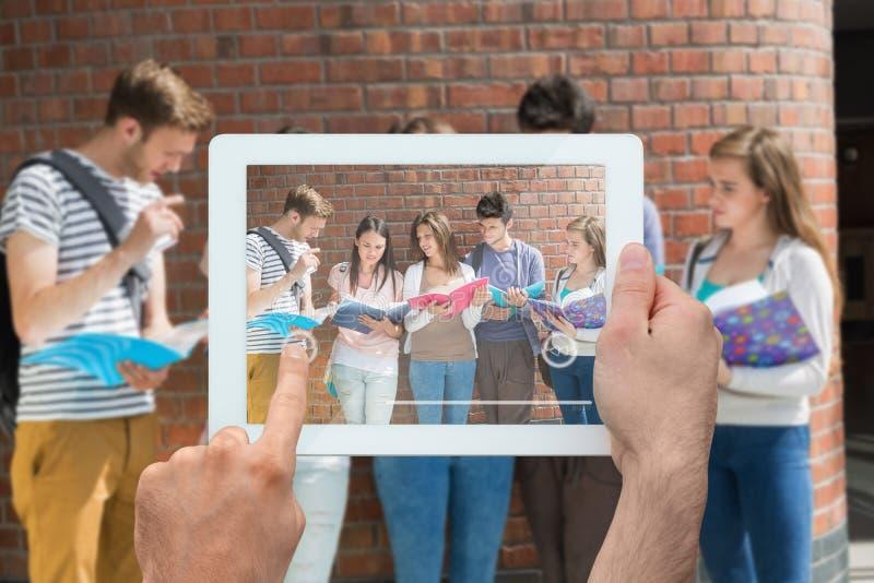 Σύνθετη εικόνα του PC ταμπλετών εκμετάλλευσης χεριών στοκ φωτογραφία