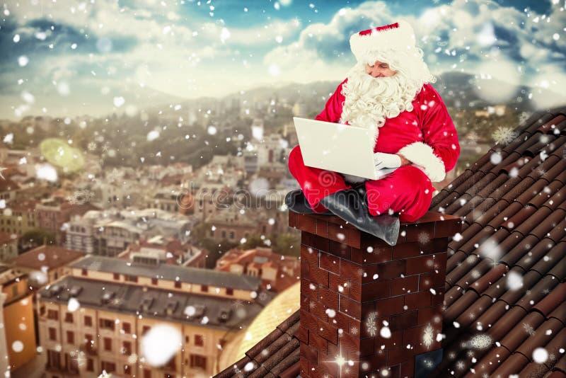 Σύνθετη εικόνα του santa που κάθεται και που χρησιμοποιεί το lap-top του στοκ φωτογραφίες