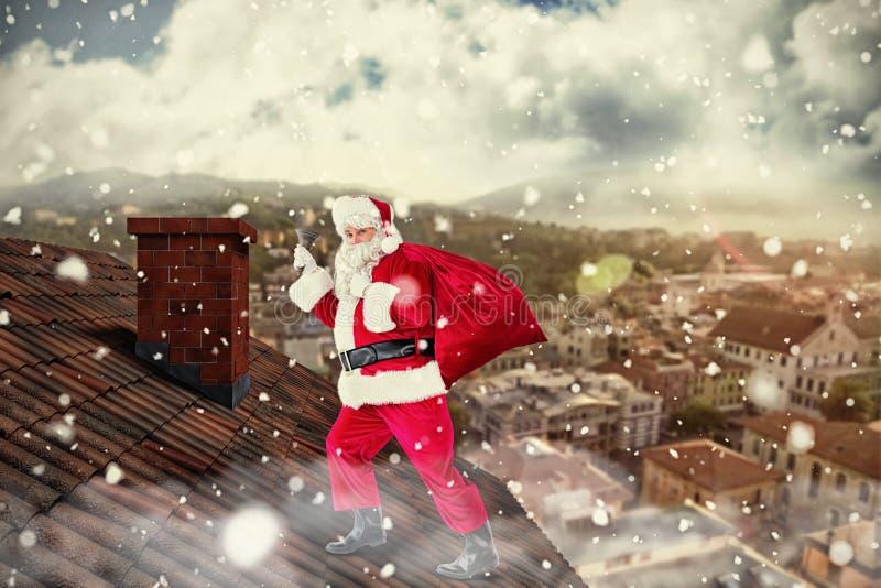 Σύνθετη εικόνα του santa που περπατά με το σάκο και το κουδούνι του στοκ εικόνες